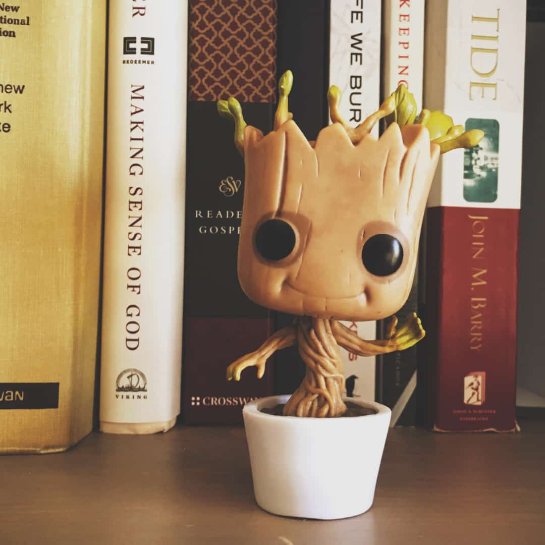 Cute baby groot planter in a white pot with some books behind