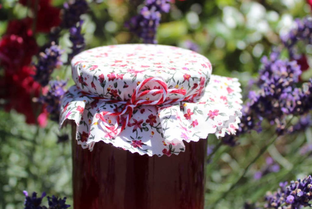 Mason jar with lavender jelly in it with a background of lavender flowers.