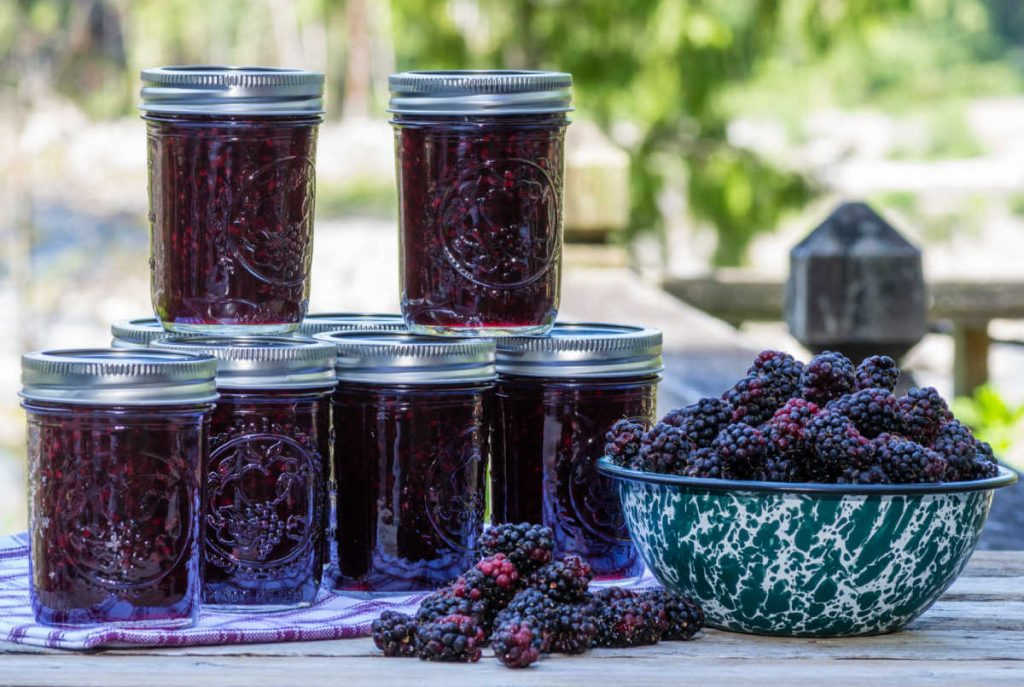 jars of marionberry jam stacked on a table with a bowl of marionberries next to them.