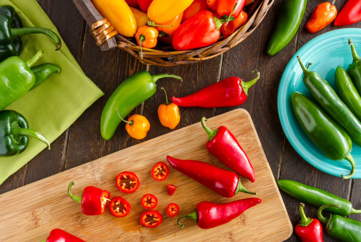 various types of peppers on a cutting board.